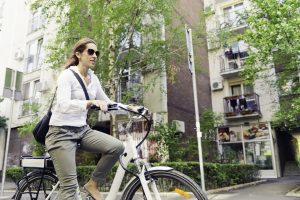 Kvinne sykler på elsykkel.